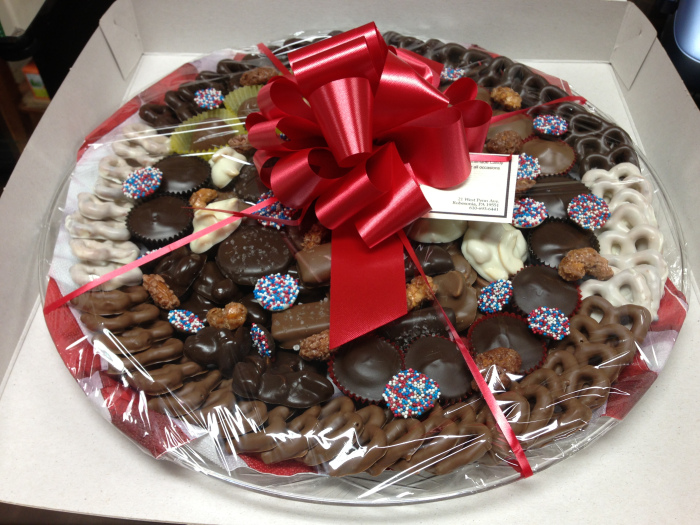 Assorted chocolates on tray wrapped with red ribbon